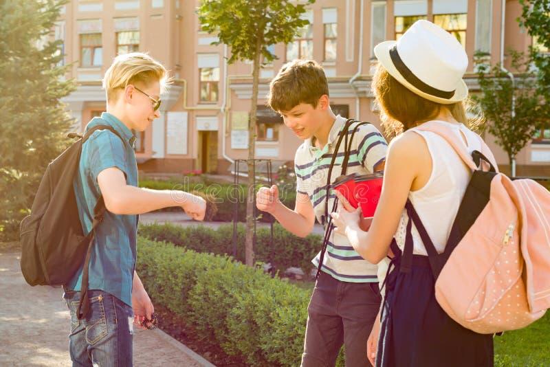 Gruppen av lyckliga tonåringar 13, 14 år som promenerar stadsgatan, vänner hälsar sig på ett möte royaltyfria foton