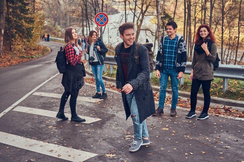 Gruppen av lyckliga vänner av turister står på sidan av vägen och fångar en övergående bil arkivfoto
