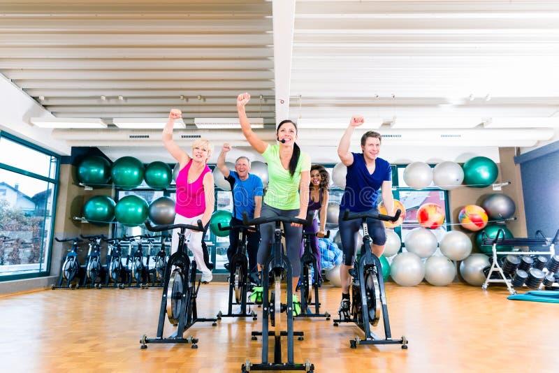 Gruppen av män och kvinnor som rotera på kondition, cyklar i idrottshall fotografering för bildbyråer