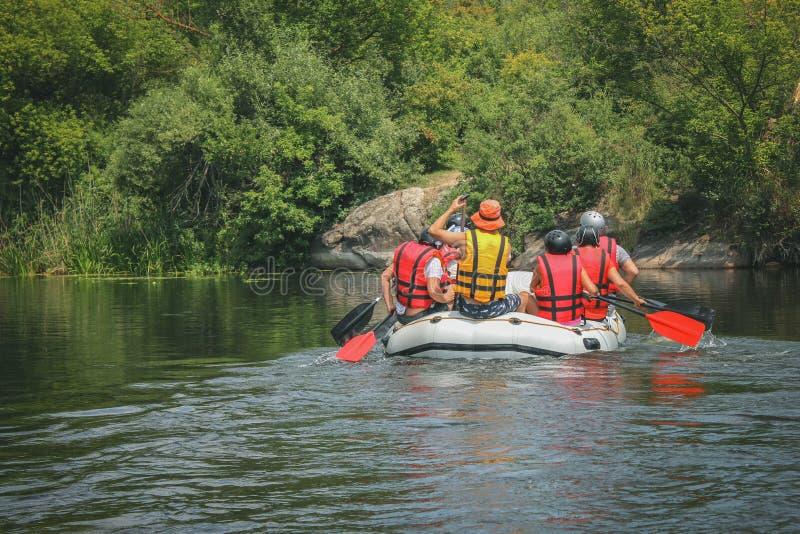Gruppen av män och kvinnor, tycker om vatten som rafting aktivitet på floden fotografering för bildbyråer