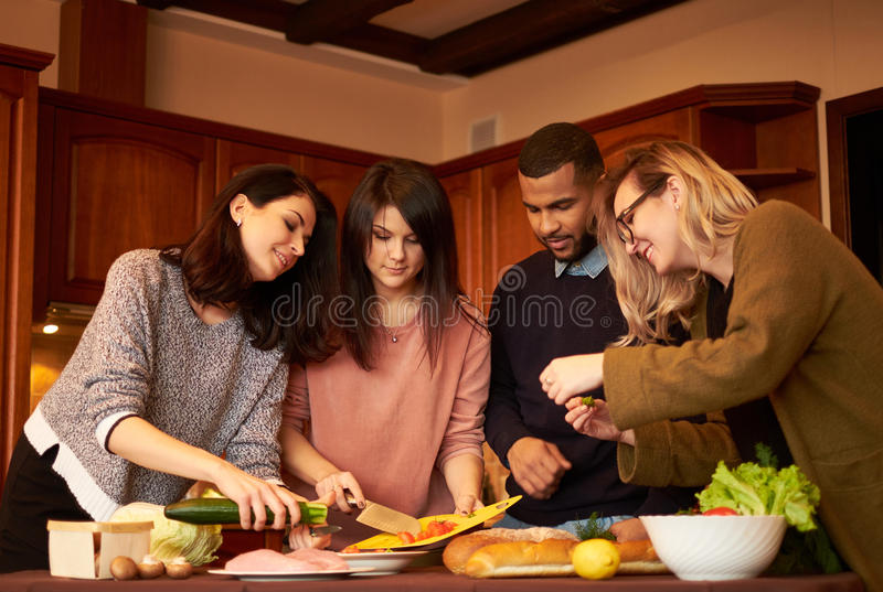 Gruppen av mång- etniska unga vänner i kök förbereder sig för parti royaltyfria foton