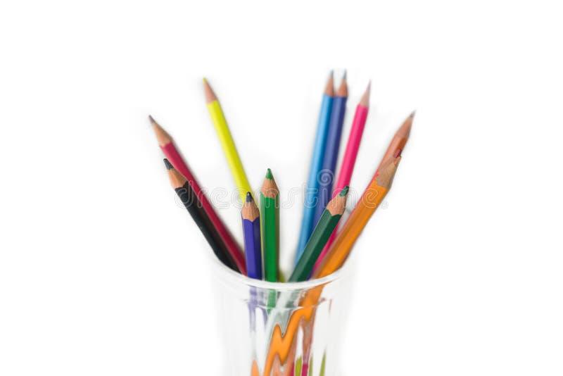 gruppen av Mång--färgade blyertspennor i ett genomskinligt exponeringsglas rånar isolerat på vit arkivfoto