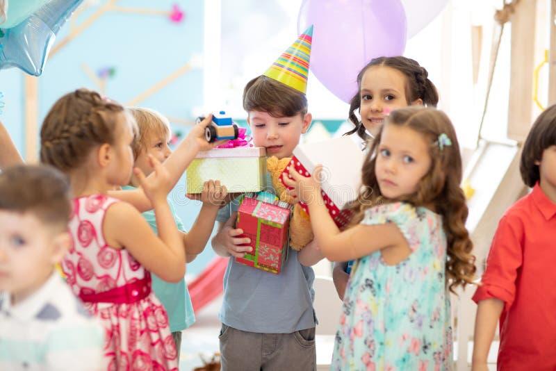 Gruppen av mångfaldbarn festar tillsammans Ungar som ger gåvaaskar till pojken under födelsedagpartiet i daycare eller klubba royaltyfria bilder