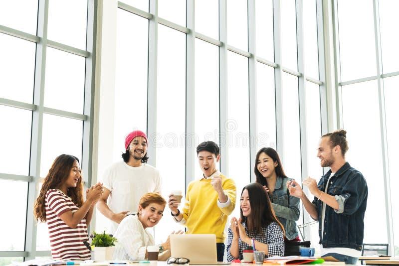 Gruppen av mångfaldfolk Team att le och gladlynt i framgångarbete med bärbara datorn på det moderna kontoret arkivfoto