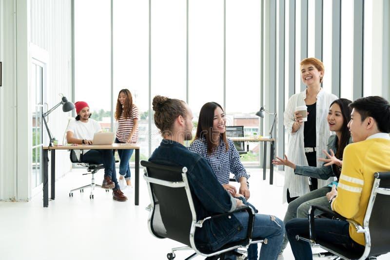Gruppen av mångfaldfolk Team att le och att skratta och gladlynt i litet möte på det moderna kontoret royaltyfri foto