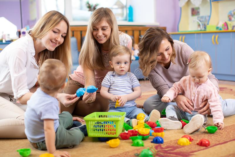 Gruppen av mödrar med behandla som ett barn på Playgroup arkivbild
