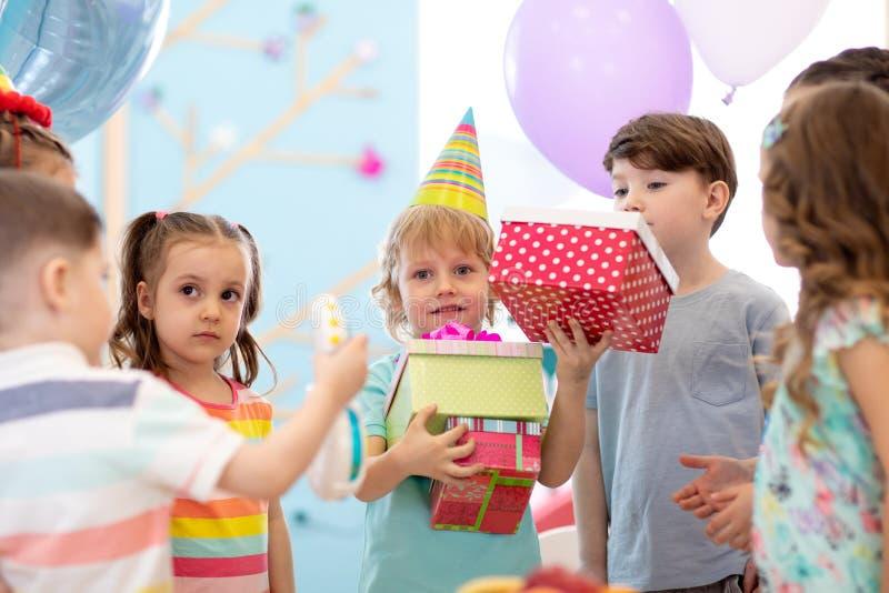 Gruppen av m?ngfaldbarn festar tillsammans Ungar som ger g?vaaskar till pojken under f?delsedagpartiet i daycare eller klubba arkivfoton