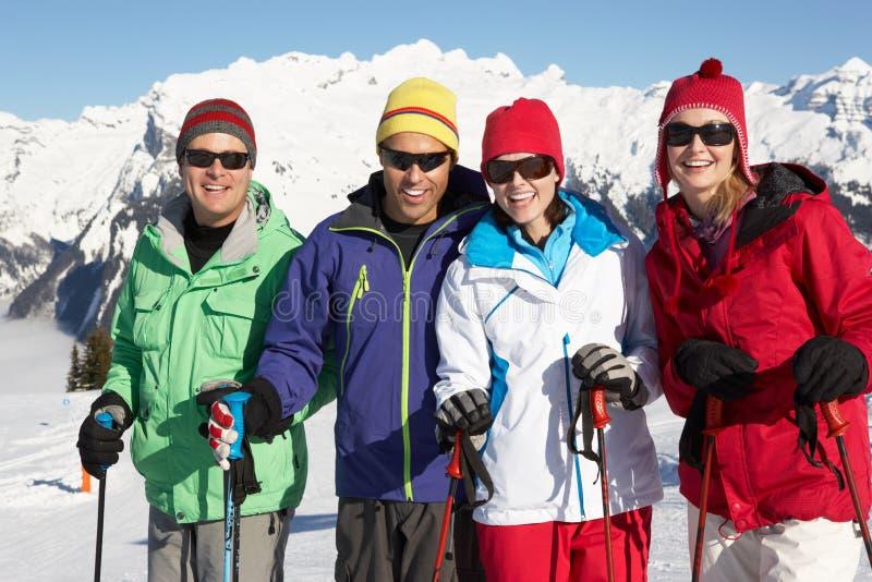 Gruppen av medelåldriga par skidar på ferie royaltyfri foto