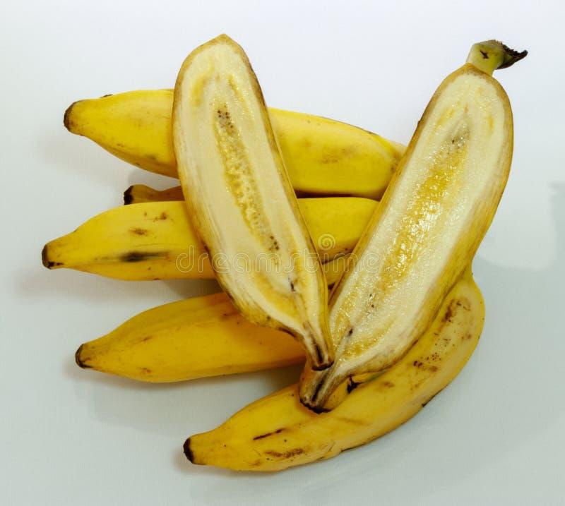 Gruppen av mogna gula bananer samman med en cutted i mitt arkivfoto