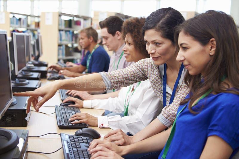 Gruppen av mogna studenter som arbetar på datorer med, handleder royaltyfri fotografi