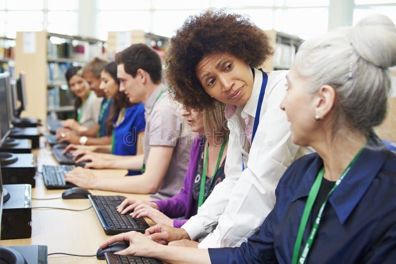 Gruppen av mogna studenter som arbetar på datorer med, handleder royaltyfria foton