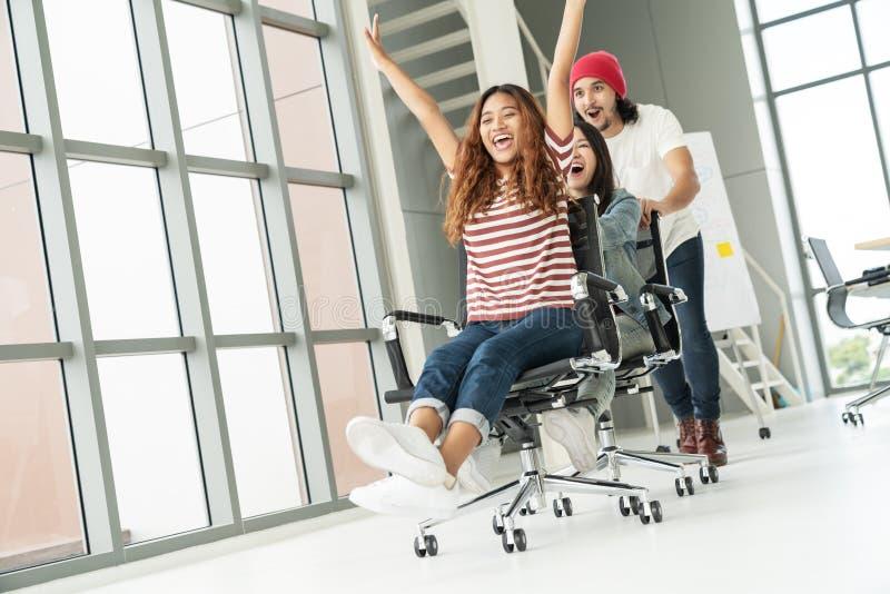 Gruppen av multietnisk ung idérik teamwork som har gyckel som i regeringsställning skrattar och ler, presiderar att skjuta Cowork arkivfoto