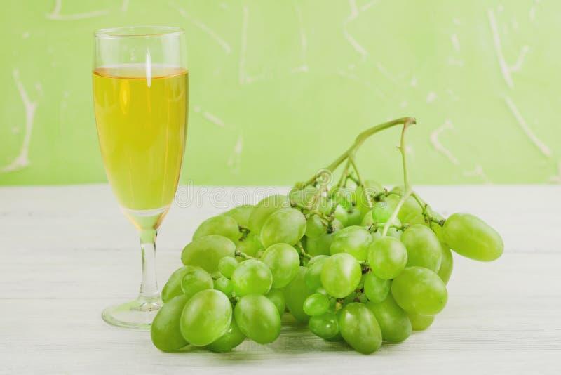 Gruppen av nya mogna gröna druvor near genomskinligt och bräckligt glass mycket av vin på gamla trävita plankor royaltyfri bild