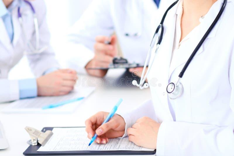 Gruppen av okända manipulerar arbete på sjukhuset, medan sitta på tabellen Teamwork- och framgångbegrepp i medicin royaltyfria foton