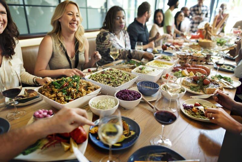 Gruppen av olikt folk har lunch tillsammans arkivbild