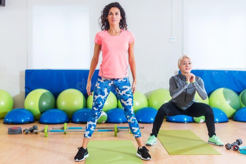 Gruppen av passformkvinnor som övar göra squattingövningar som utarbetar deras ben, tränga sig in i konditionstudio arkivfoton