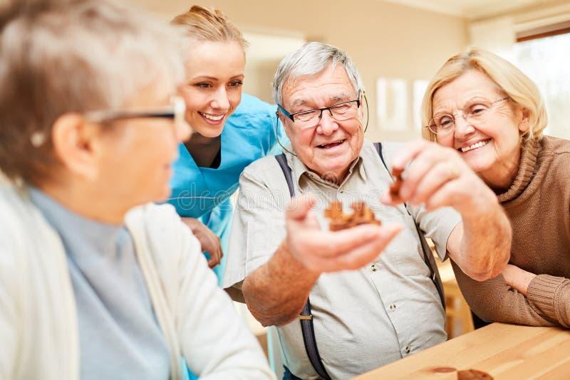 Gruppen av pension?rer spelar med ett tr?pussel arkivbilder