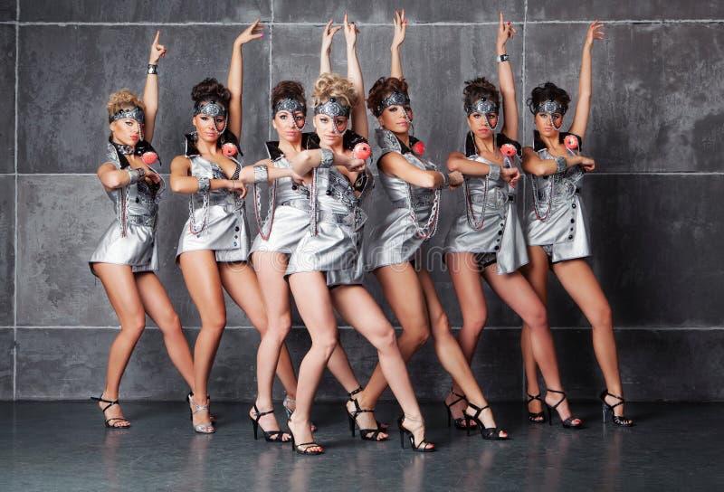 Gruppen av sju lyckliga gulliga flickor i silver gå-går dräkten royaltyfri bild