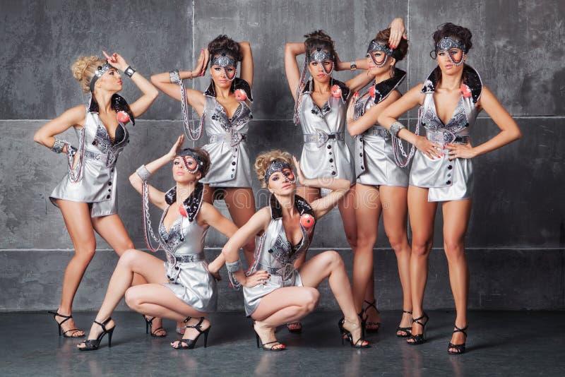 Gruppen av sju lyckliga gulliga flickor i silver gå-går dräkten arkivbild