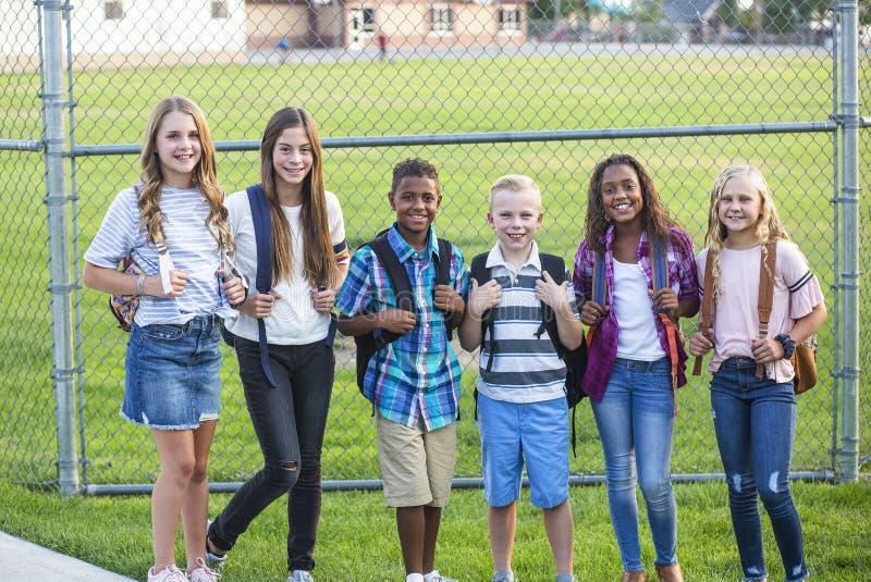 Gruppen av skolan lurar att le, medan stå i en grundskolalekplats arkivbilder