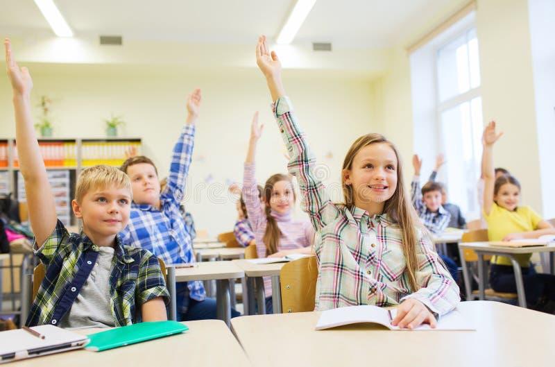 Gruppen av skolan lurar att lyfta händer i klassrum royaltyfri bild