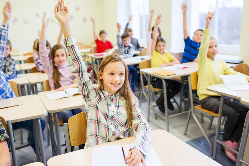 Gruppen av skolan lurar att lyfta händer i klassrum royaltyfria foton