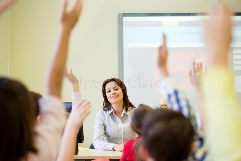 Gruppen av skolan lurar att lyfta händer i klassrum royaltyfri foto