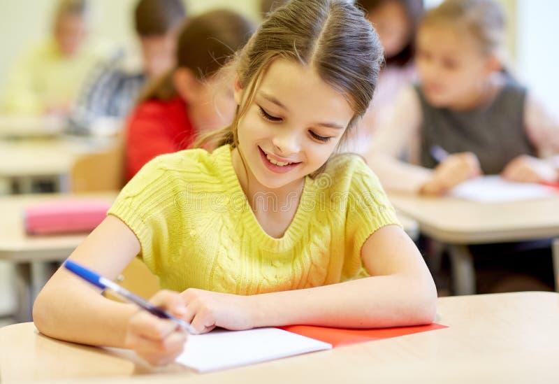 Gruppen av skolan lurar handstilprovet i klassrum royaltyfria bilder