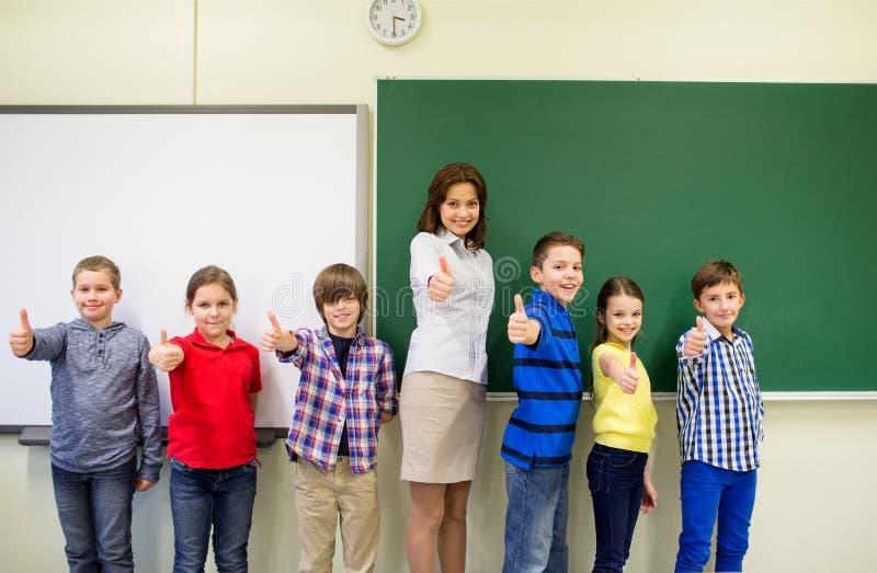 Gruppen av skolaungar och lärarevisning tummar upp royaltyfria foton