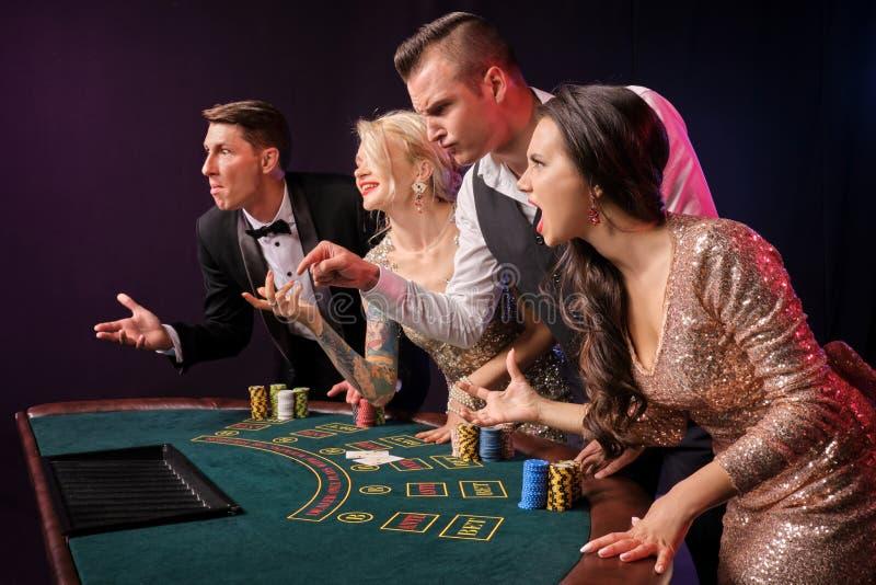 Gruppen av stilfulla rika vänner spelar poker på kasinot royaltyfria foton