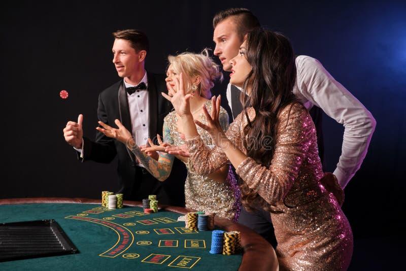 Gruppen av stilfulla rika vänner spelar poker på kasinot arkivbilder