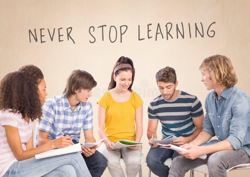 Gruppen av studenter som sitter av aldrig, stoppar framme att lära text royaltyfria foton