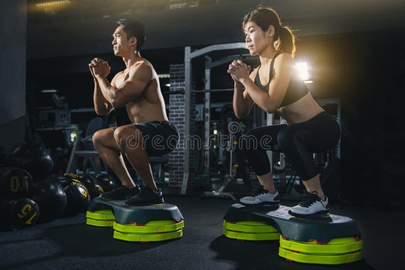 Gruppen av sunt konditionfolk i idrottshall, unga par utarbetar på idrottshallen, attraktiv kvinna, och den stiliga muskulösa man royaltyfri bild