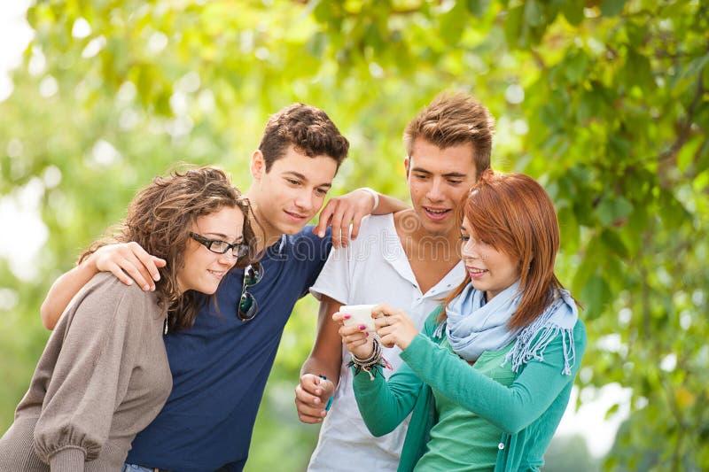 Gruppen av tonåringar som poserar för en grupp, fotograferar royaltyfri fotografi