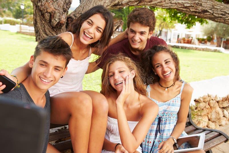 Gruppen av tonåringar som sitter på bänken som tar Selfie parkerar in fotografering för bildbyråer