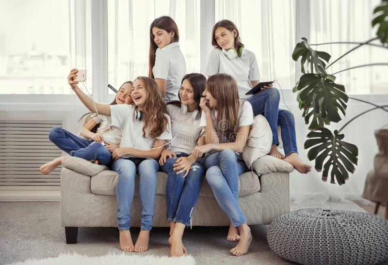 Gruppen av tonårs- flickor gör en selfie Ungar med telefoner, minnestavlor och hörlurar royaltyfria foton