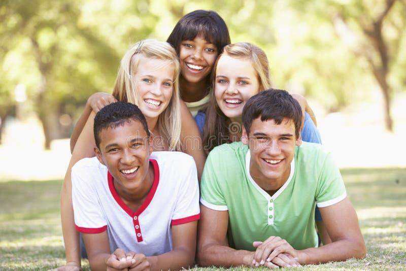 Gruppen av tonårs- vänner som har gyckel parkerar in royaltyfria foton