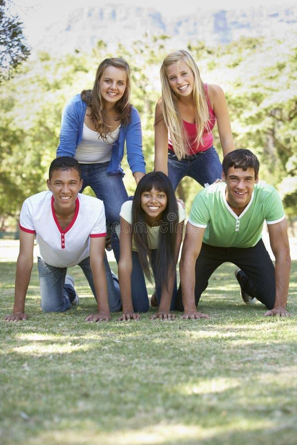 Gruppen av tonårs- vänner som har gyckel parkerar in royaltyfri fotografi