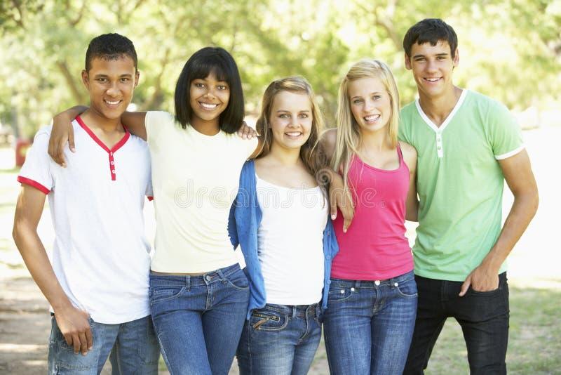 Gruppen av tonårs- vänner som in står, parkerar arkivbilder
