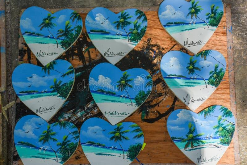 Gruppen av trähjärta formade souvenir med landskap av Maldiverna på den fotografering för bildbyråer