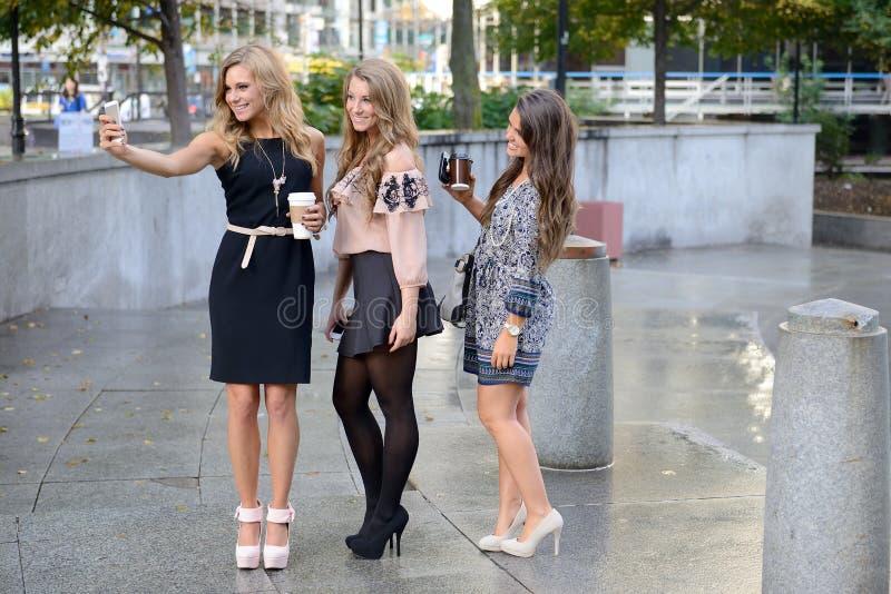 Gruppen av tre härliga unga kvinnor tar en selfie royaltyfri fotografi