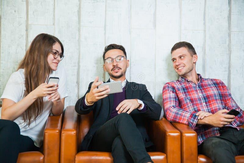 Gruppen av tre smartphones för ungdomarhåll talar och ler arkivfoto