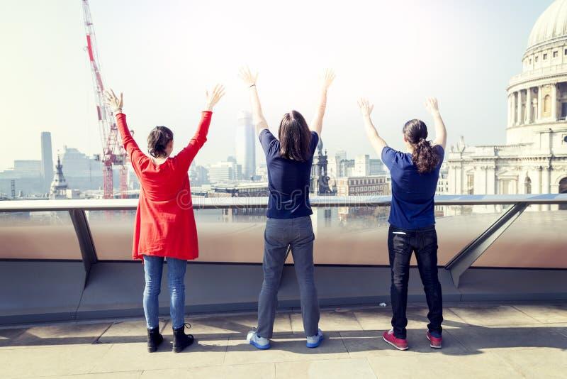 Gruppen av tre unga vänner lyfter deras armar royaltyfri foto