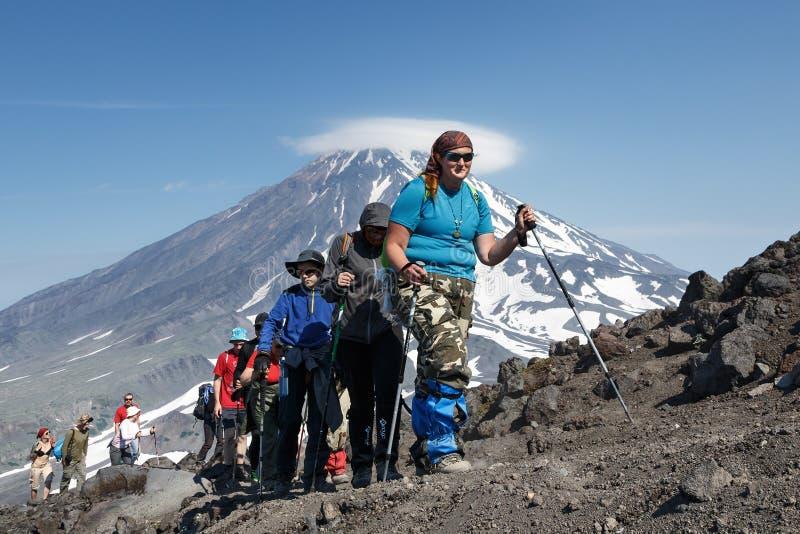 Gruppen av turister går att fotvandra och att klättra till överkanten av vulkan arkivfoto