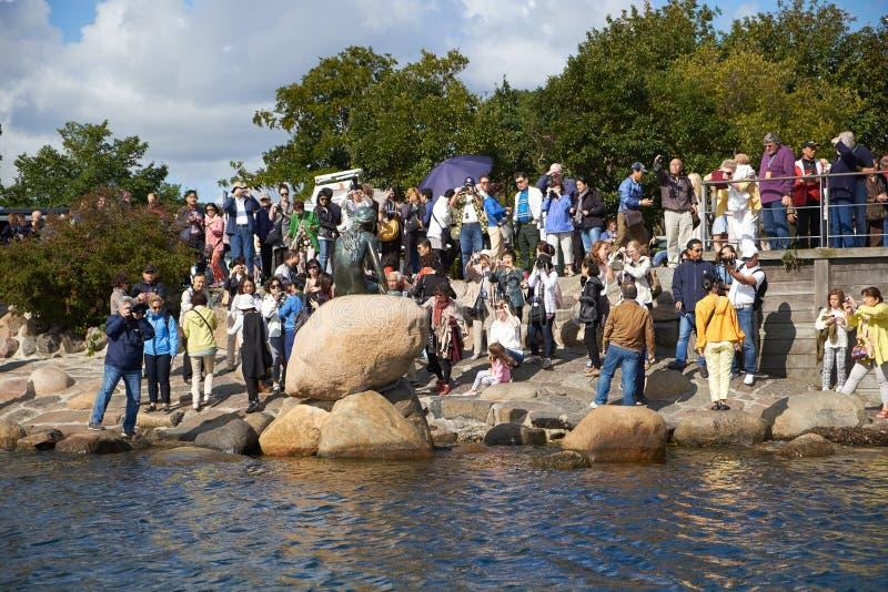 Gruppen av turister near den lilla sjöjungfrustatyn royaltyfria foton