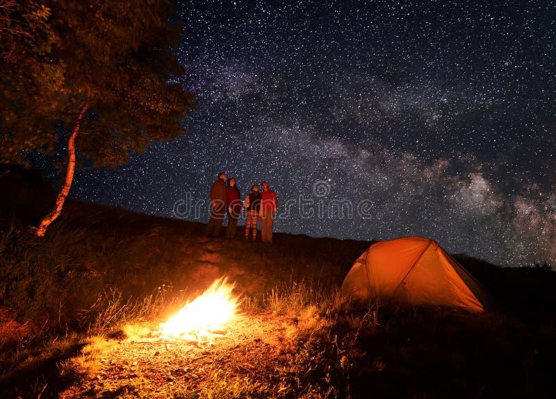 Gruppen av turister tycker om ovanlig himmel som beströs med ljusa stjärnor under campa för natt royaltyfri fotografi