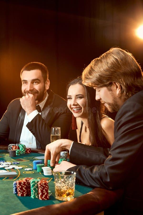 Gruppen av ung de rika spelar poker i kasinot royaltyfria bilder