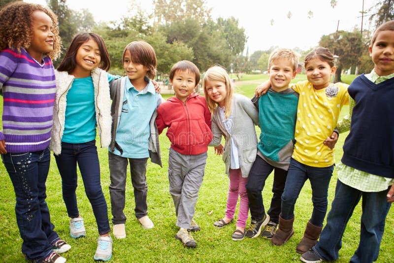 Gruppen av unga barn som ut hänger i, parkerar arkivfoto