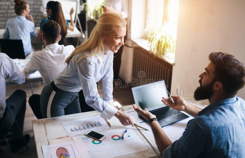 Gruppen av unga businesspeople eller formgivare arbetar med nytt startprojekt i regeringsst?llning arkivbilder