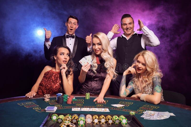 Gruppen av unga förmögna vänner spelar poker på en kasino royaltyfri bild